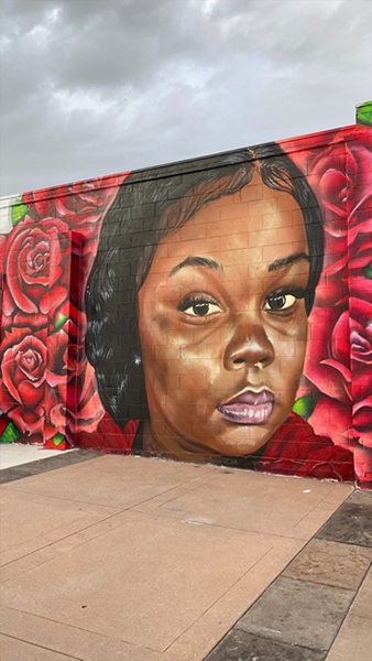 Photograph of a mural of Breonna Taylor surrounded by roses