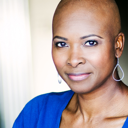 Better Hart - black woman with no hair and bright blue sweater