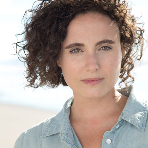 White woman with dark brown short curly hair