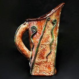 hand-made pitcher with green decorative elements