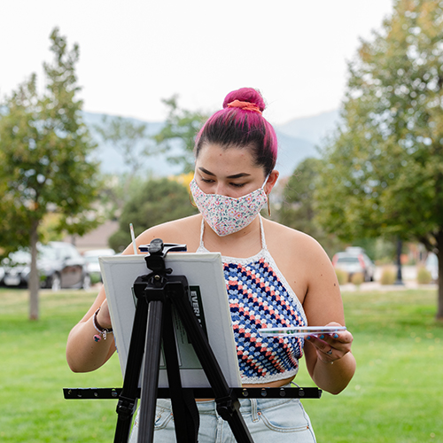 CC student with mask drawing at an easel outside